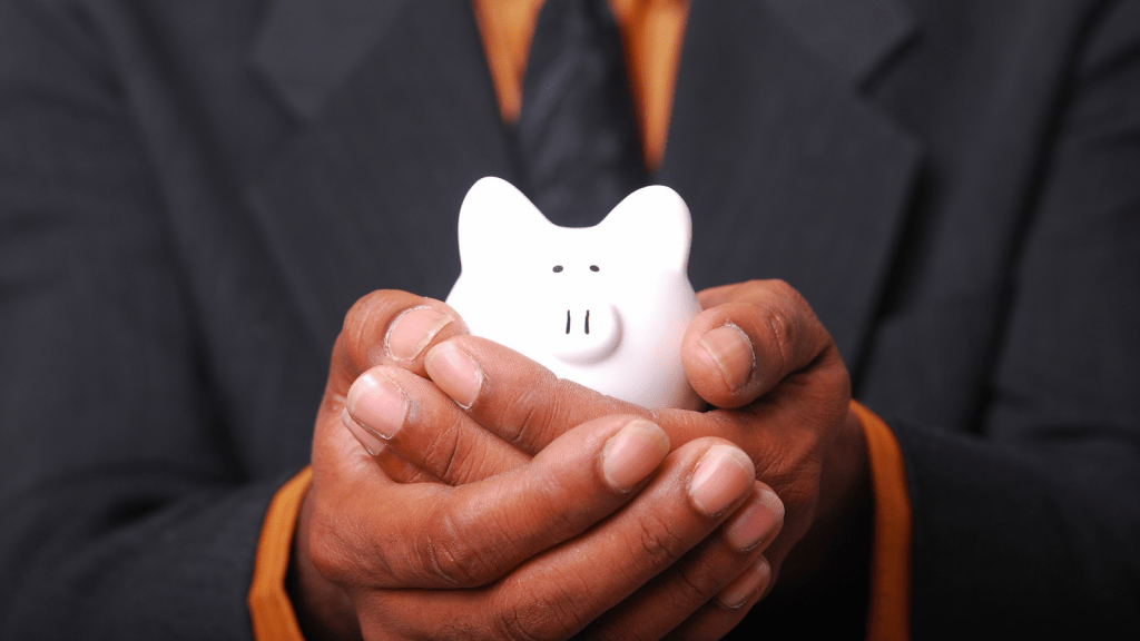 Man in a suit and tie holding a piggy bank.