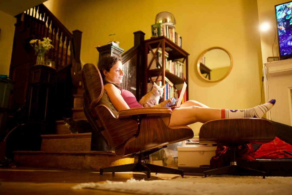 Picture of woman working on her laptop with a cat nearby.