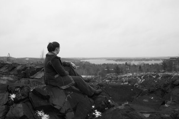 Photo of Julie sitting on a rock, overlooking the city of Sudbury